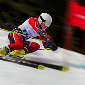 Male ski racer passing red gate